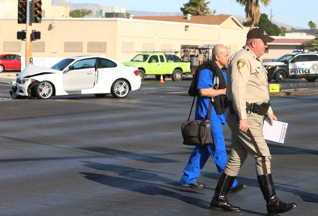 A Las Vegas police officer escorts the driver of a white BMW, involved in a crash with Metro police patrol car, at Rancho and Vegas drives where one officer was taken to the hospital on Wednesday, ...