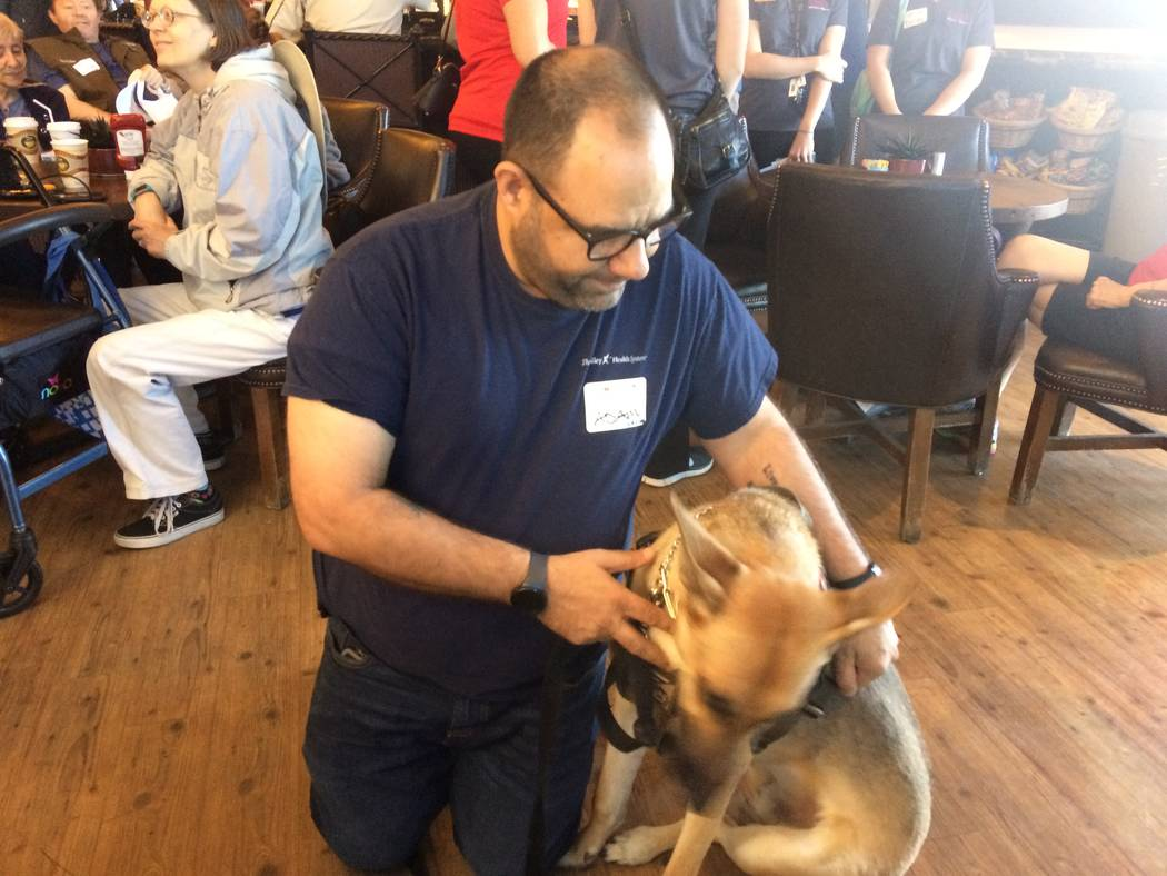 Adam Alberico pets his service dog, Westley, who is trained to nose-tap a sensor on Alberico's wrist at the first sign of trouble. The sensor signals a 24/7 call center. Alberico worked in Summe ...