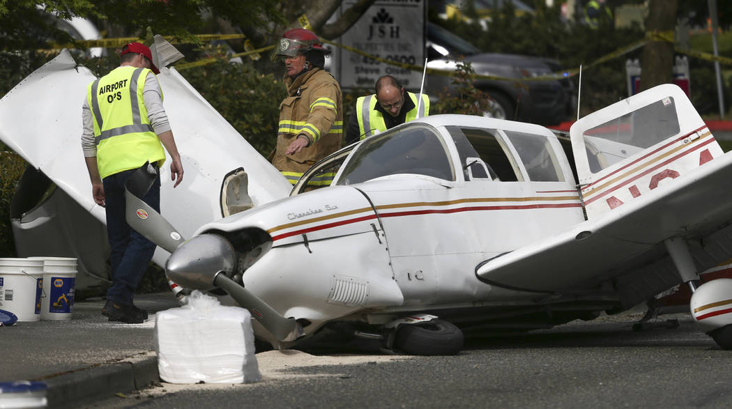 A firefighter and two Snohomosh County Airport workers look over a plane that crashed on Harbor Point Boulevard Southwest and Mukilteo Speedway, after losing power on takeoff from Paine Field on T ...