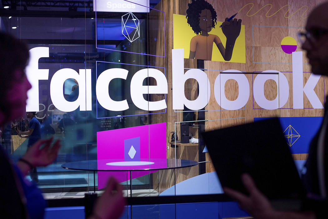 Conference workers speak in front of a demo booth at Facebook's annual F8 developer conference in San Jose, Calif. on April 18, 2017. (Noah Berger/AP)