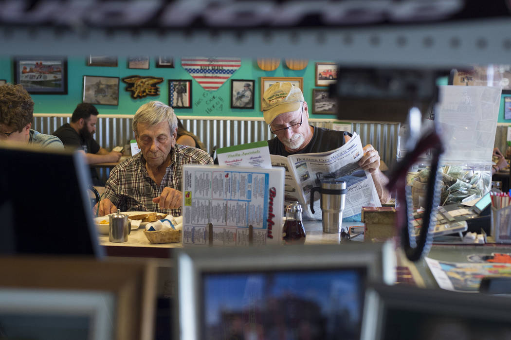 Sandy Nelson, left, eats his lunch while friend David Dilley, right, reads the newspaper at The Coffee Cup on Thursday, May 4, 2017, in Boulder City. Nelson, one of acts for Dillinger Block Party, ...
