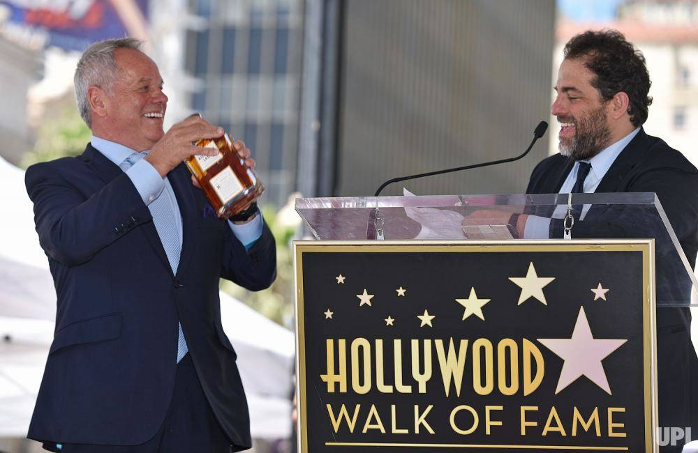 Wolfgang Puck receives a gift from Brett Ratner during the former's Hollywood Walk of Fame star ceremony Wednesday, April 26, 2017, in the Hollywood section of Los Angeles. (UPI.com)