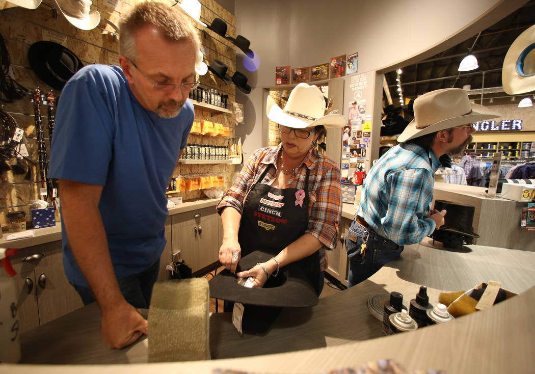 Jill Cook demonstrates how to attach a stampede string to a hat to her customer Glenn Sneep, left, as Michael Hull helps another customer at Boot Barn store on Thursday, May 4, 2017, in Las Vegas. ...