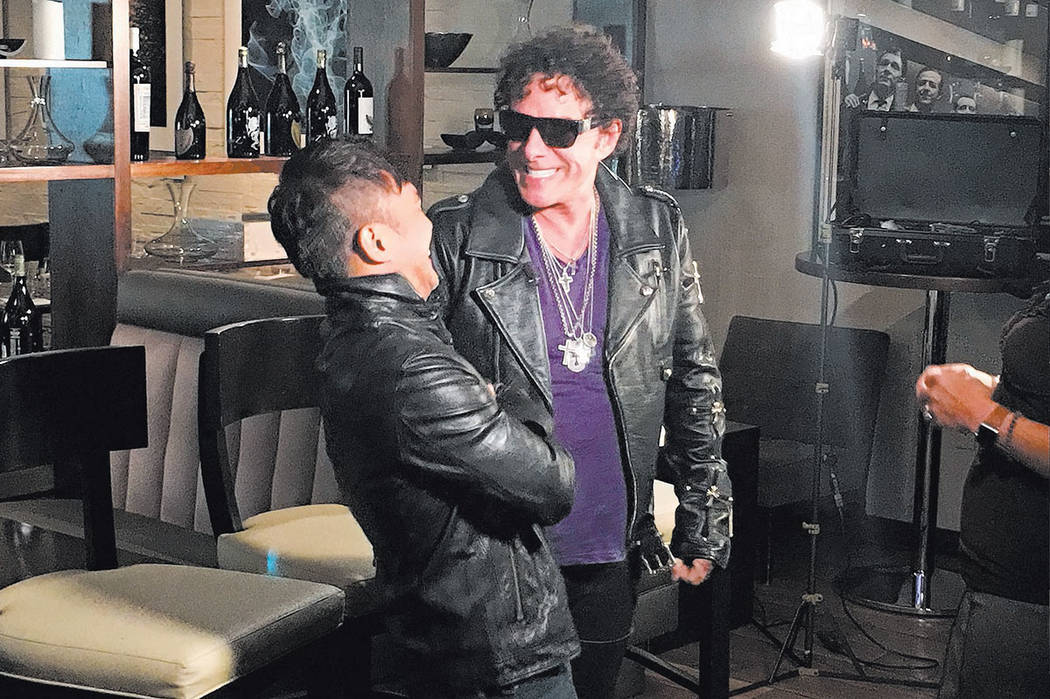 Journey guitarist Neal Schon jokes with singer Arnel Pineda during an appearance at the Hard Rock Hotel on May 3, 2017. (John Katsilometes/Las Vegas Review-Journal)