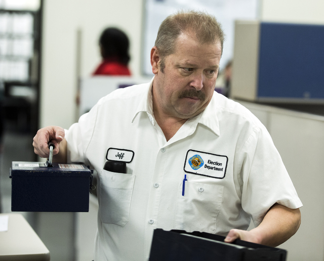 Clark County Election worker Jeff Martin carries medal boxes contain data files during a voter recount at the Clark County Election Department office, 965 Trade Drive in North Las Vegas, on Monday ...