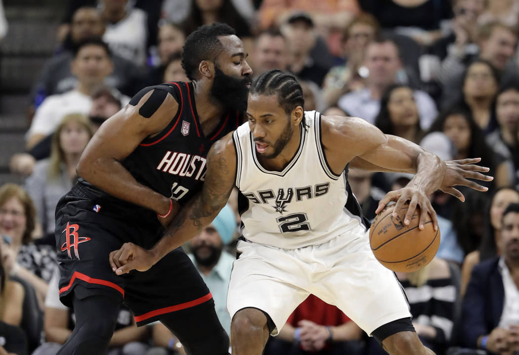 San Antonio Spurs forward Kawhi Leonard (2) works for an opportunity to the basket as Houston Rockets' James Harden, left, defends during the first half of Game 2 in a second-round NBA basketball  ...