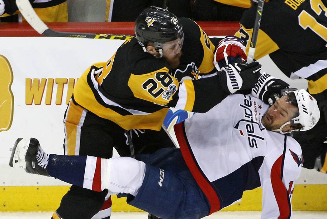 Pittsburgh Penguins' Ian Cole (28) checks Washington Capitals' Justin Williams (14) off the puck during the third period of Game 4 in an NHL Stanley Cup Eastern Conference semifinal hockey game in ...
