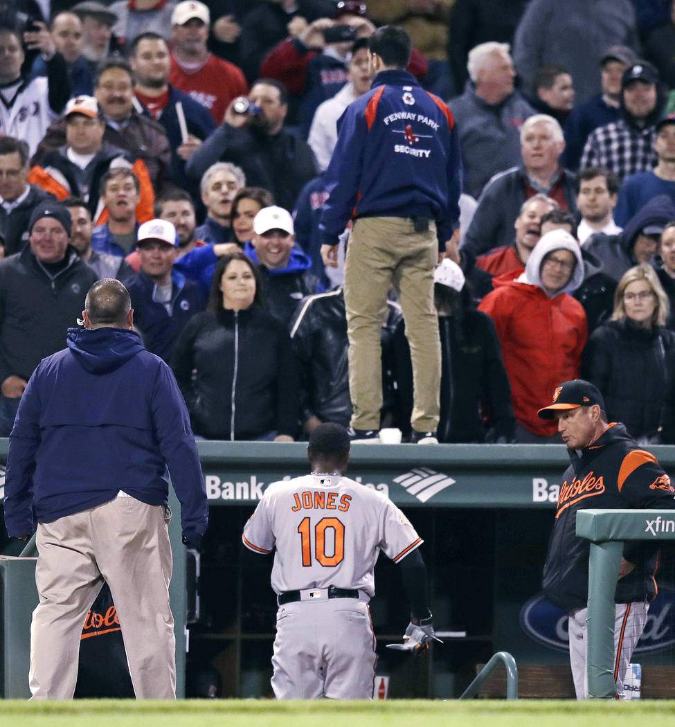 Security guard stands on the dugout roof and another on the field as Boston Red Sox fans watch Baltimore Orioles' Adam Jones head to the clubhouse after he was ejected for arguing a strikeout duri ...