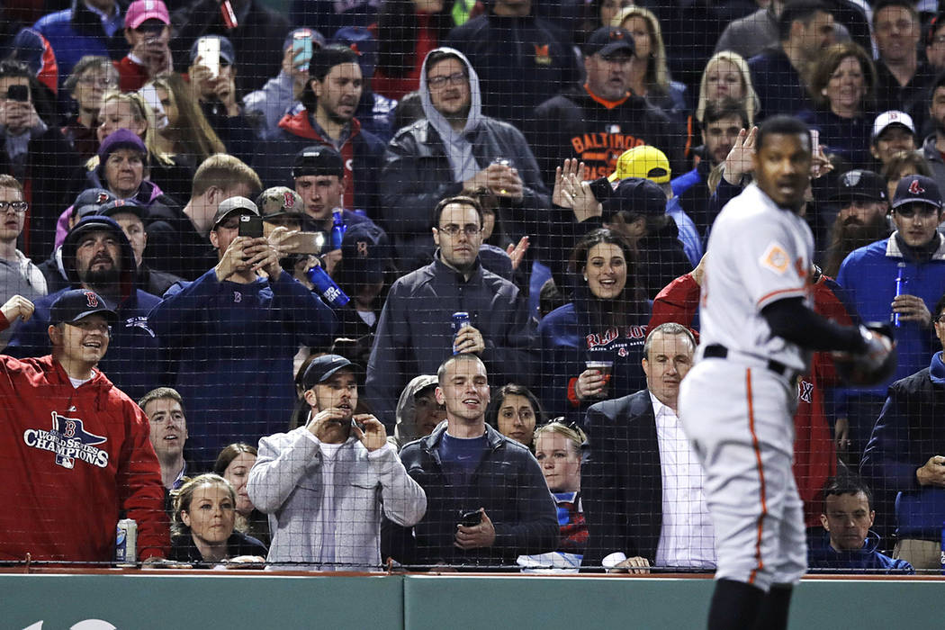 Boston Red Sox fans taunt and take pictures of Baltimore Orioles' Adam Jones after he was ejected for arguing a strikeout call during the fifth inning of a baseball game at Fenway Park in Boston,  ...