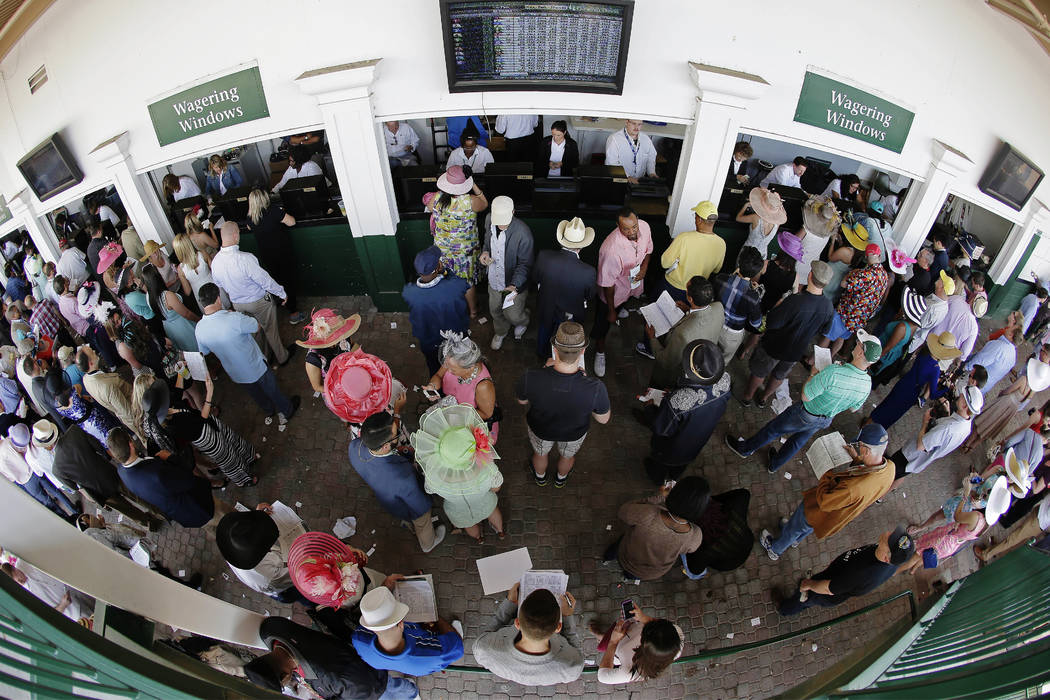 FILE - In this May 3, 2014, file photo, taken with a fisheye lens, fans line up to place bets before the 140th running of the Kentucky Derby horse race at Churchill Downs in Louisville, Ky. Church ...
