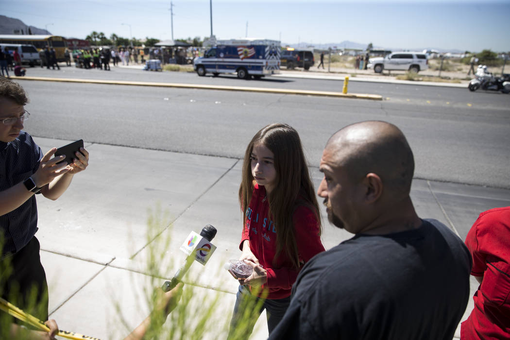 Kristiana Tenchavez, 13, is interviewed with her father Vincent after she was released on scene of a school bus crash near the intersection of Carey Avenue and Nellis Boulevard on Thursday, May 4, ...