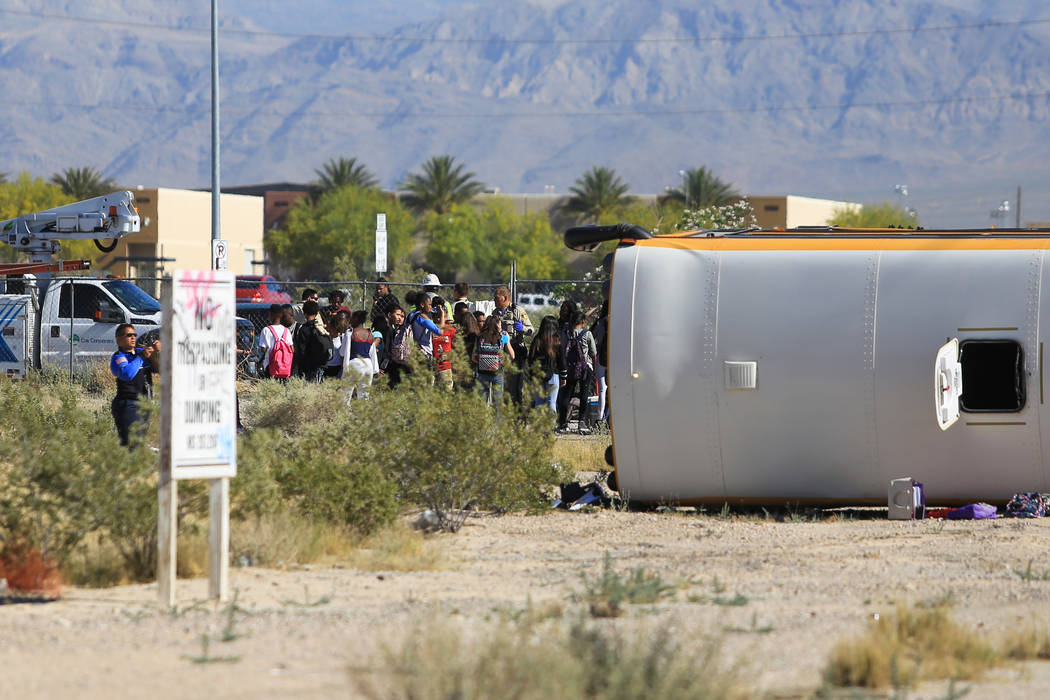 Students stand near a rolled-over school bus that was involved in a crash near the intersection of Carey Avenue and Nellis Boulevard on Thursday, May 4, 2017, in Las Vegas. Brett Le Blanc Las Vega ...