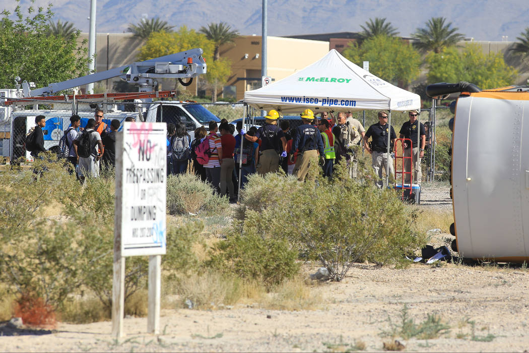 Students and emergency personnel stand near a rolled-over school bus that was involved in a crash near the intersection of Carey Avenue and Nellis Boulevard on Thursday, May 4, 2017, in Las Vegas. ...