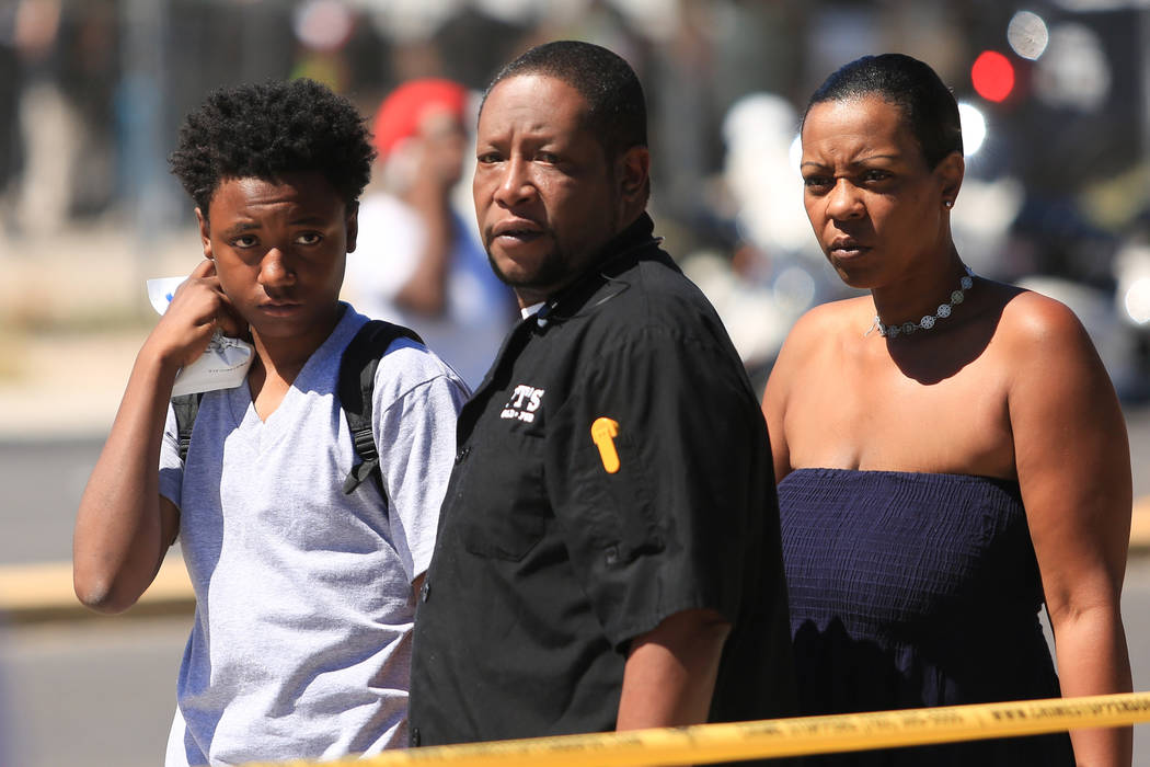 A family stands inside the crime scene tape at the scene of a crash that caused a school bus to roll over on Thursday, May 4, 2017, in Las Vegas. Brett Le Blanc Las Vegas Review-Journal @bleblancphoto