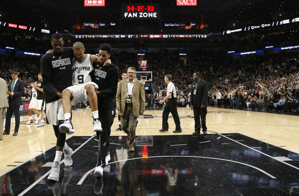 San Antonio Spurs guard Tony Parker (9) is carried off the court after being injured during the second half of Game 2 of a second-round NBA basketball playoff series against the Houston Rockets, W ...