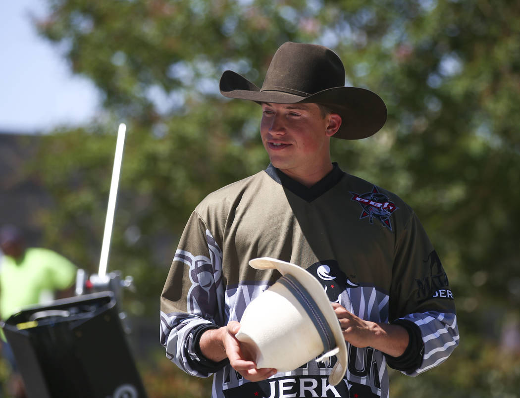 Professional Bull Riders bullfighter Cody Webster takes a look at a cowboy hat belonging to Dale Brisby, not pictured, during a break in filming a promotional advertisement for sponsor Matador Jer ...