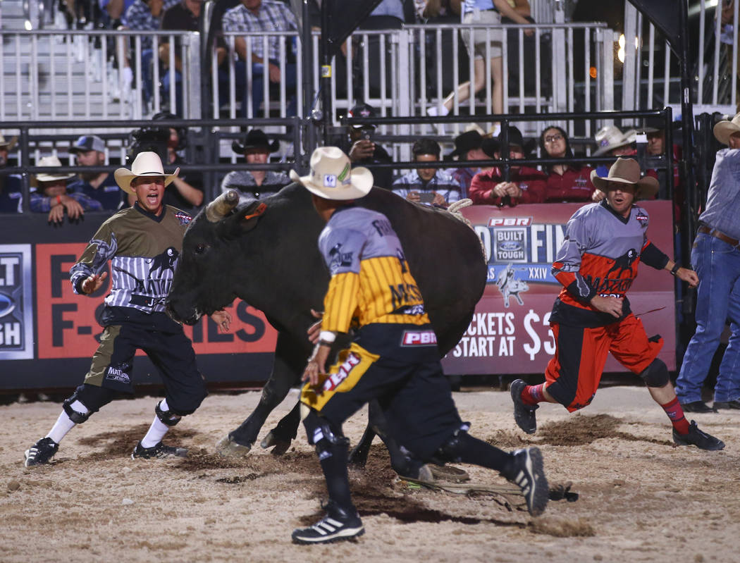 "Professional Bull Riders bullfighters, from left, Cody Webster, Frank Newsom and Seth ""Shorty"" Gorham distract bull Element 79, ridden by Jake Gowdy, during the Last Cowboy Standing event at Las V ..."