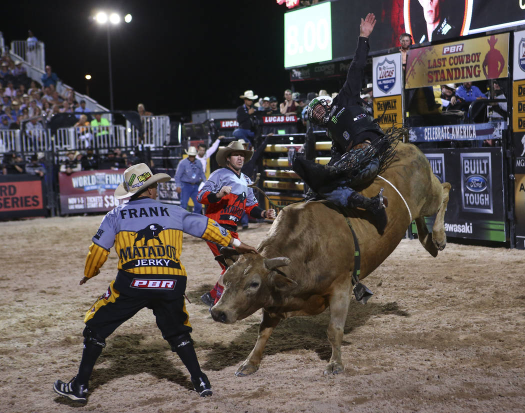 "Professional Bull Riders bullfighters, Frank Newsom, left, and Seth ""Shorty"" Gorham watch as Gage Gay rides Cowboy Phil during the Last Cowboy Standing event at Las Vegas Village ..."