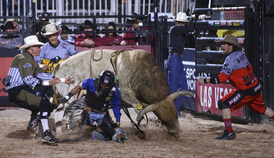 "Professional Bull Riders bullfighters, from left, Cody Webster, Frank Newsom, and Seth ""Shorty"" Gorham work to save Rubens Barbosa after he was bucked off of Ol' Rusty Boy during ..."