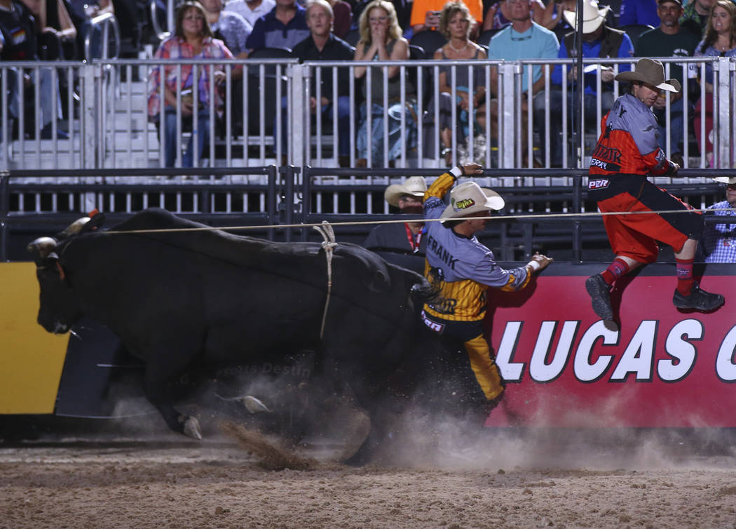"Professional Bull Riders bullfighters Frank Newsom and Seth ""Shorty"" Gorham jump out of the path of Element 79 during the Last Cowboy Standing event at Las Vegas Village in Las V ..."