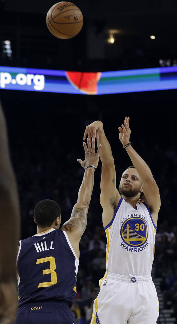 In this April 10, 2017, file photo, Golden State Warriors guard Stephen Curry (30) shoots over Utah Jazz guard George Hill (3) during the first half of an NBA basketball game in Oakland, Calif. Go ...