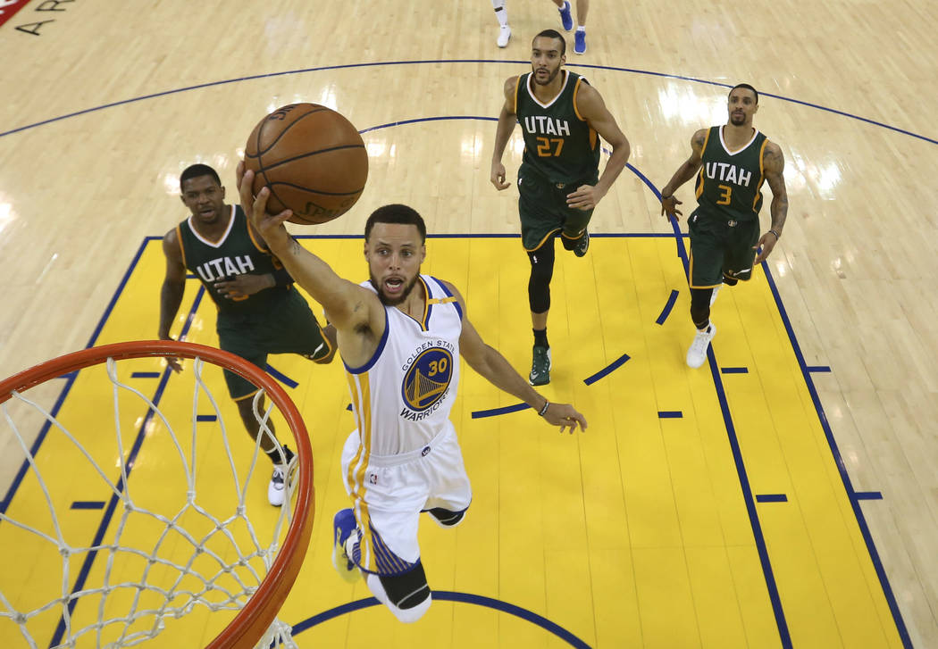 Golden State Warriors' Stephen Curry (30) drives to the basket past Utah Jazz's Joe Johnson, left, Rudy Gobert (27) and George Hill (3) during the second half in Game 1 of an NBA basketball second ...