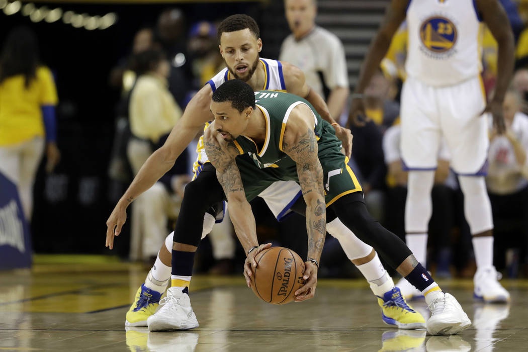 Utah Jazz's George Hill, bottom, is defended by Golden State Warriors' Stephen Curry during the first half in Game 1 of an NBA basketball second-round playoff series, Tuesday, May 2, 2017, in Oakl ...