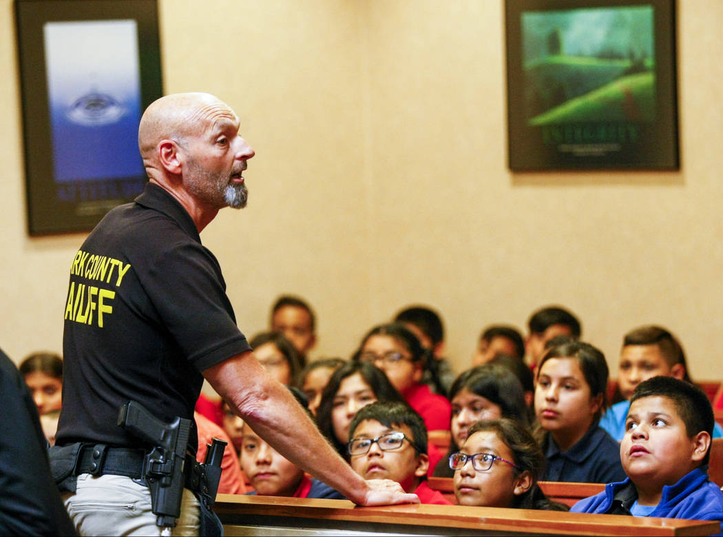 "Ron Wright, judicial bailiff for Judge Natalie Tyrrell, talks with fifth graders from C.P. Squires Elementary School attend a mock trial as a part of the ""Kids in the Court"" prog ..."