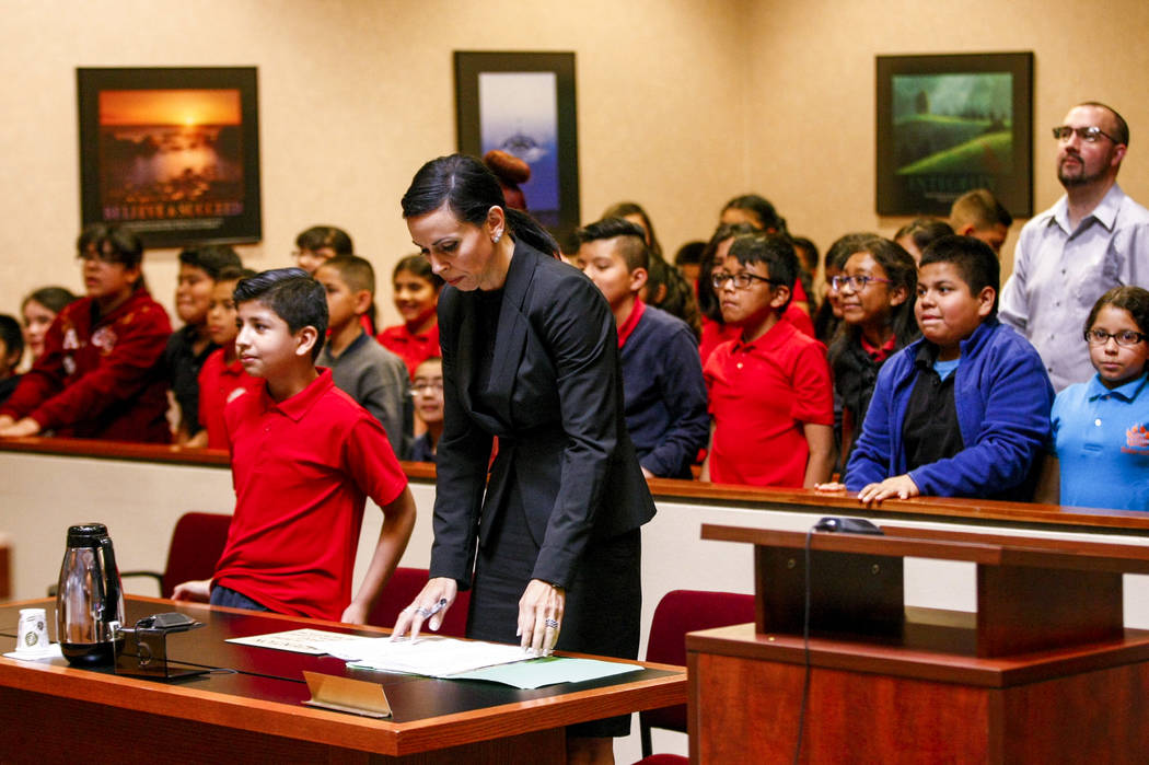 "Attorney Ivette Maningo rises with fifth graders from C.P. Squires Elementary School as Judge Natalie Tyrrell enters the courtroom during a mock trial as a part of the ""Kids in the Court& ..."