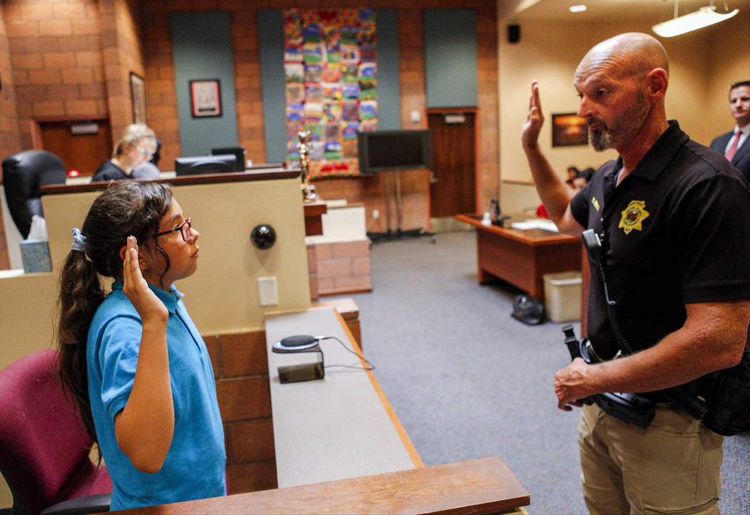 Ron Wright, judicial bailiff for Judge Natalie Tyrrell, swears in Zitlalic Salinas, the plaintiff and a fifth grader from C.P. Squires Elementary School, during a mock trial as a part of the & ...