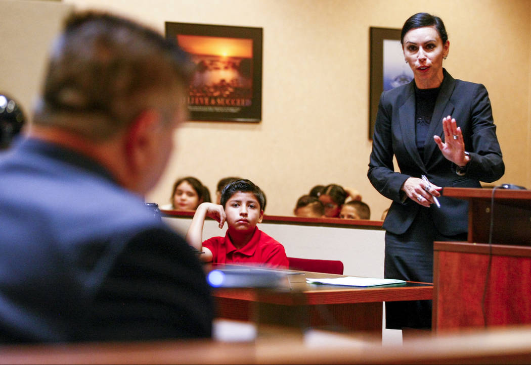 "Attorney Ivette Maningo questions Edmond Finizie, a retired North Las Vegas Police Department lieutenant, during a mock trial as a part of the ""Kids in the Court"" program at the  ..."
