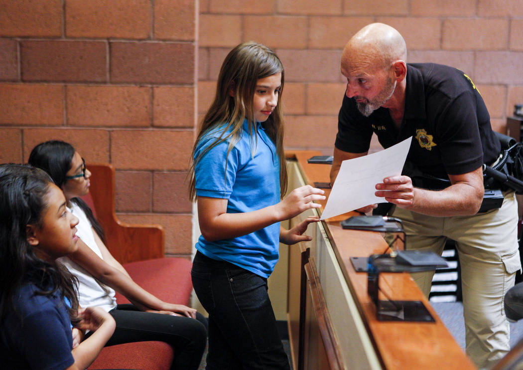 Ron Wright, judicial bailiff for Judge Natalie Tyrrell, talks about the verdict of a mock trial with fifth graders from C.P. Squires Elementary School at the North Las Vegas Justice Court on Tuesd ...