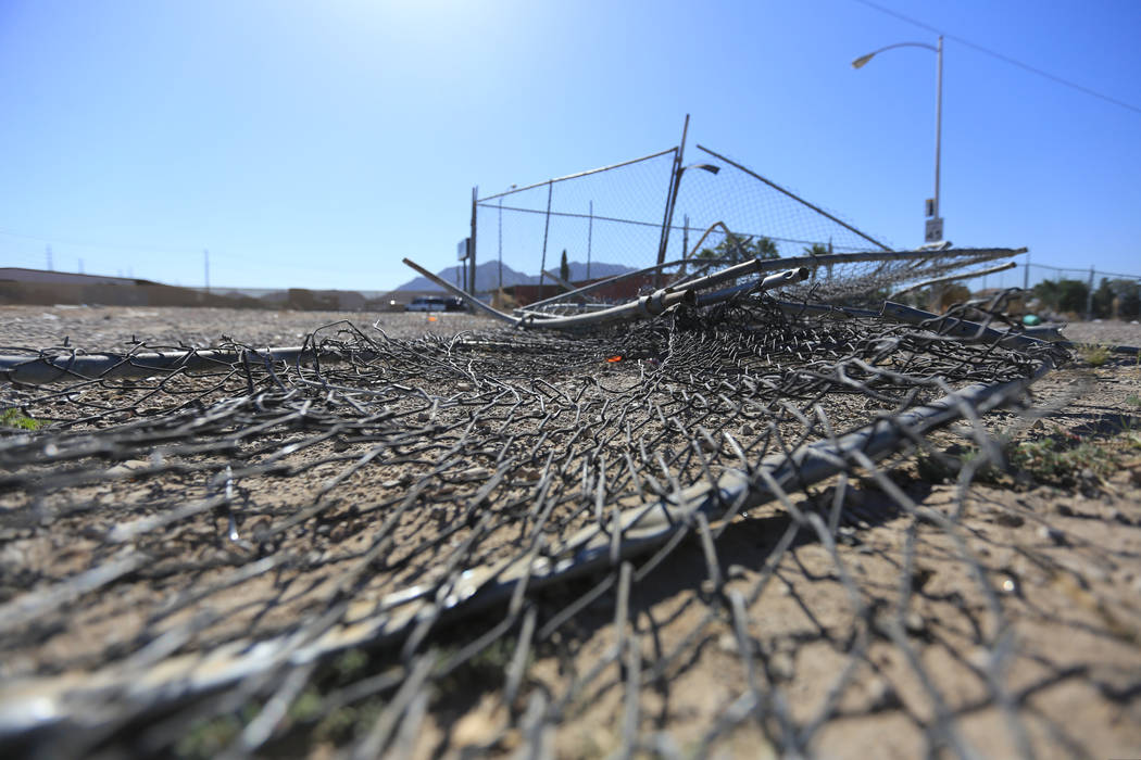 A mangled fence lies on the ground on Friday, May 5, 2017, after Thursday's wreck, when a school bus crashed through the fence and rolled on its side in Las Vegas. Brett Le Blanc Las Vegas Review- ...