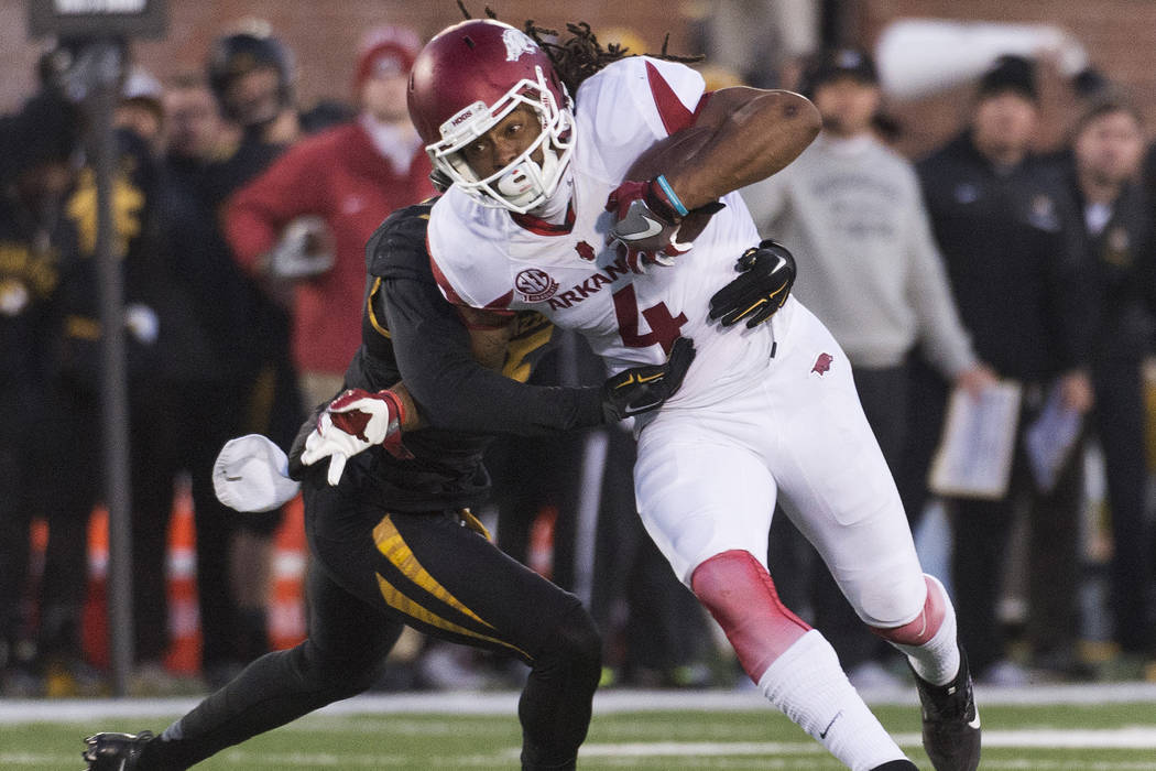Arkansas wide receiver Keon Hatcher, right, is pulled down by Missouri's John Gibson, left, during the fourth quarter of an NCAA college football game Friday, Nov. 25, 2016, in Columbia, Mo. Misso ...