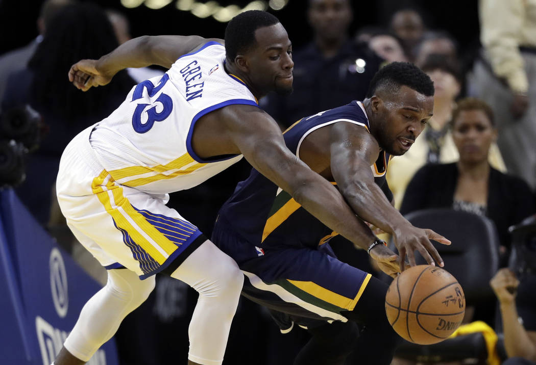 Golden State Warriors' Draymond Green, left, defends on Utah Jazz's Shelvin Mack during the first half in Game 2 of an NBA basketball second-round playoff series, Thursday, May 4, 2017, in Oakland ...