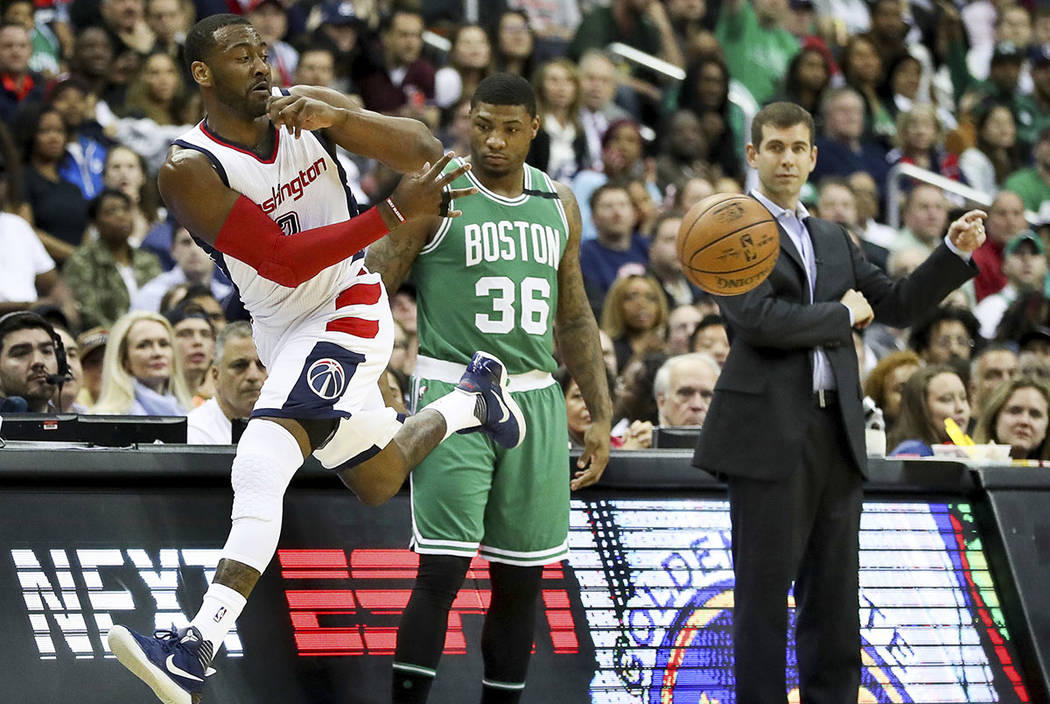 Boston Celtics guard Marcus Smart (36) and Boston Celtics head coach Brad Stevens watches as Washington Wizards guard John Wall (2) jumps out of bounds to save a loose ball during the first half i ...