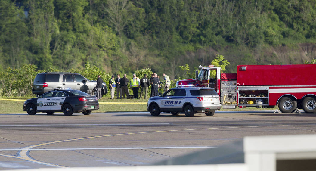 Emergency officials work near the site of a fatal plane crash at Yeager Airport in Charleston, W.Va., Friday, May 5, 2017.  A cargo plane contracted by UPS went off the runway and over a hillside  ...