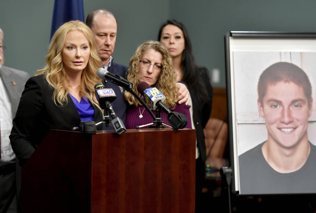 Jim and Evelyn Piazza stand by as Centre County District Attorney Stacy Parks Miller, left, announces the results of an investigation into the death of their son Timothy Piazza, seen in photo at r ...