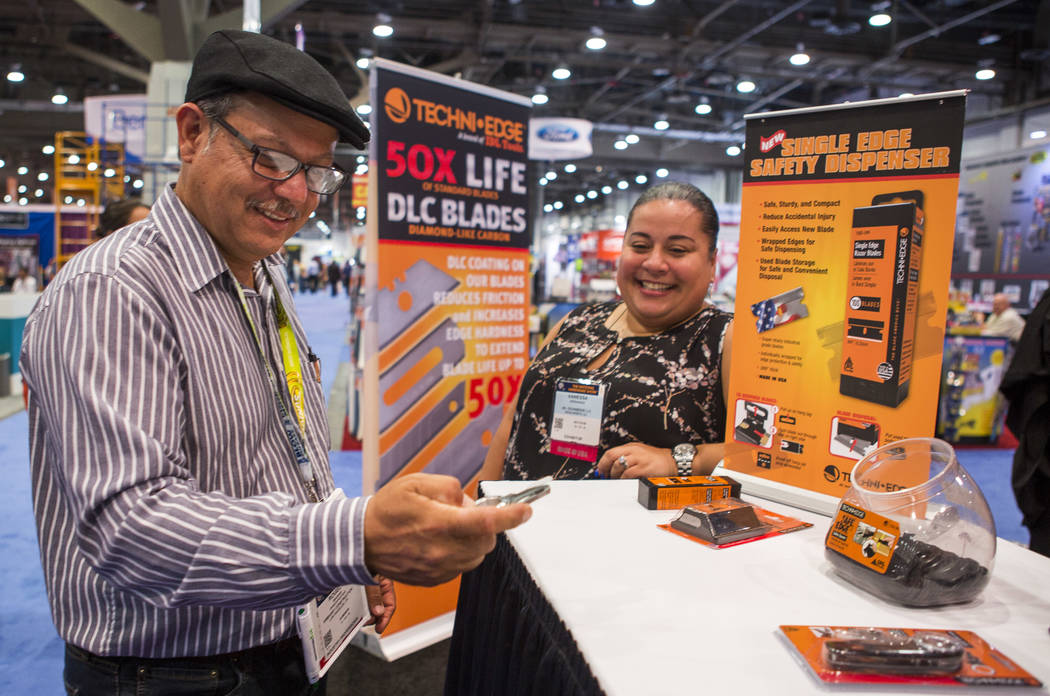 Rogelio Magana of Los Angeles, California, browses Techni Edge blades made by IDL Tools while talking with exhibitor Vanessa Hernandez at the National Hardware Show at Las Vegas Convention Center  ...