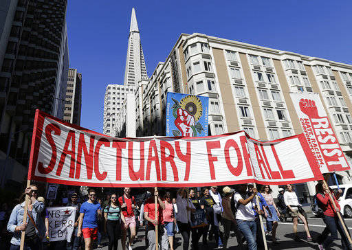 Protesters walk during a march in San Francisco, Monday, May 1, 2017.  Immigrant groups and their allies have joined forces to carry out marches, rallies and protests in cities nationwide next wee ...