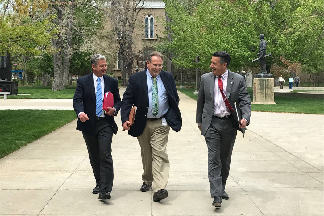 Gov. Brian Sandoval, left, Chief of Staff Mike Willden, center, and Senior Adviser Andrew Clinger walk from the Capitol to the Legislature Building Friday, May 5, 2017 to meet with Democratic Asse ...