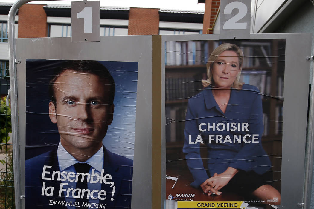 Election campaign posters for French centrist presidential candidate Emmanuel Macron and far-right candidate Marine Le Pen are displayed in front of the polling station where Marine Le Pen will vo ...