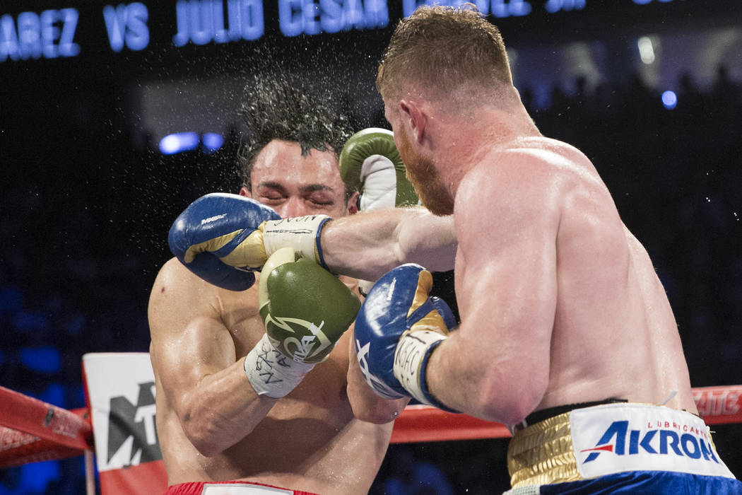 Julio Cesar Chavez Jr., left, takes a punch against Saul Canelo Alvarez in the catch weight bout at T-Mobile Arena on Saturday, May 6, 2017, in Las Vegas. Alvarez won by unanimous decision. Erik V ...