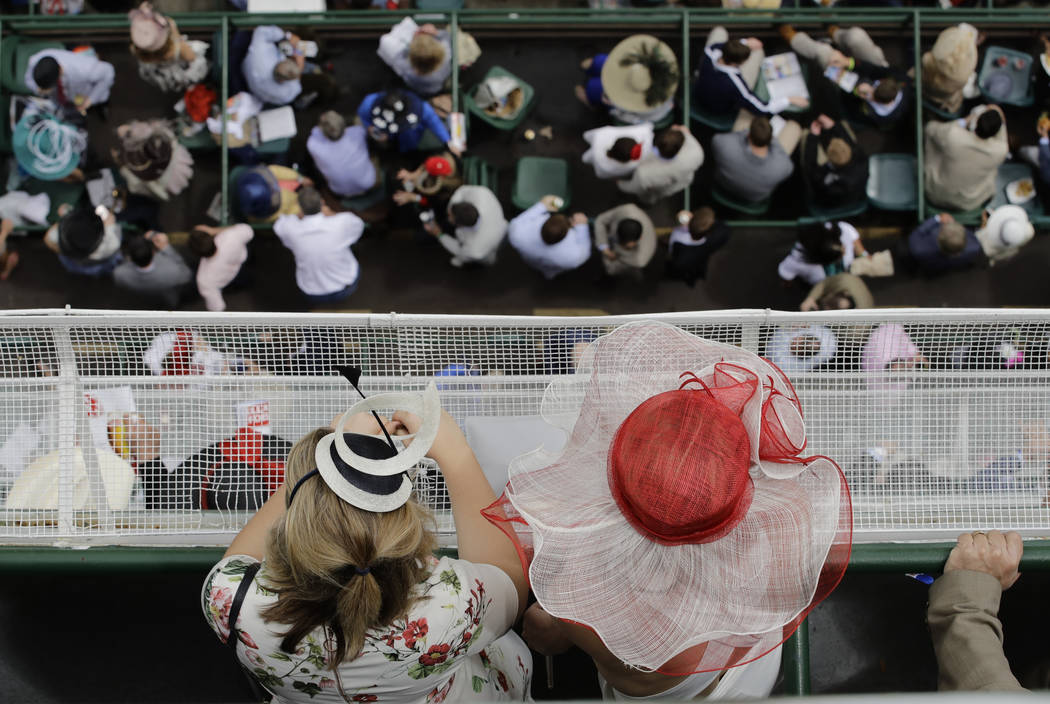 Women in hats watch a race before the 143rd running of the Kentucky Derby horse race at Churchill Downs Saturday, May 6, 2017, in Louisville, Ky. (AP Photo/Charlie Riedel)