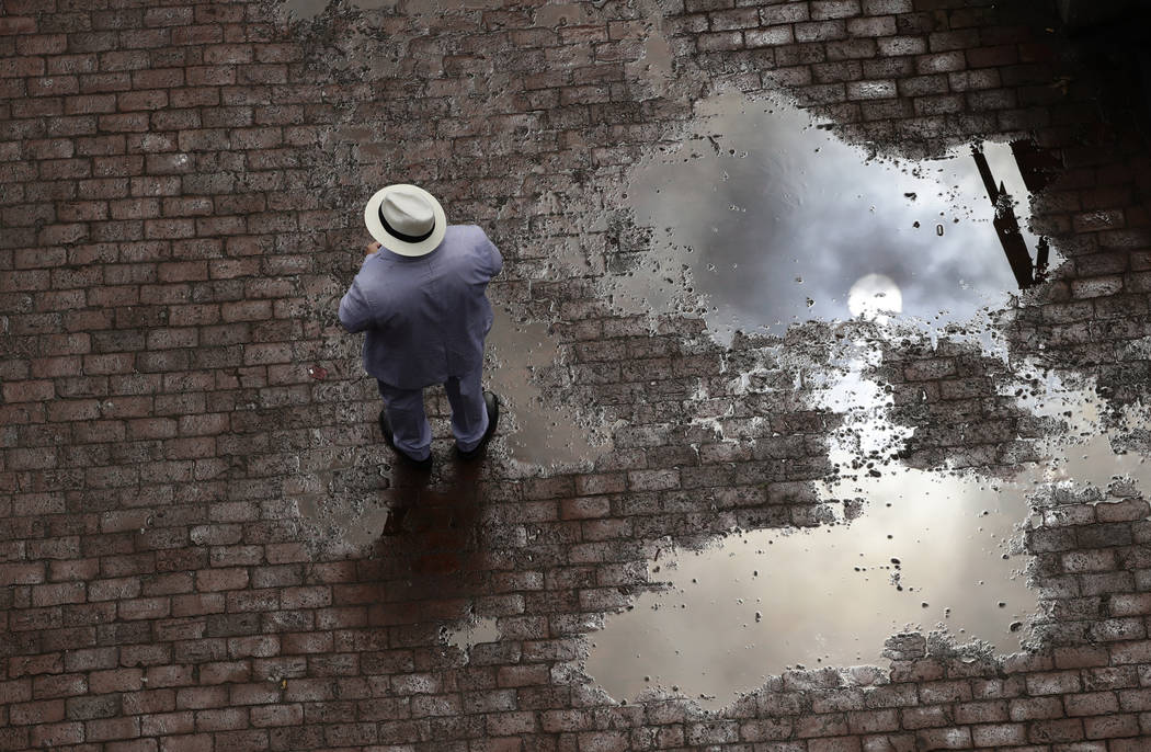 A man stands near a puddle before the 143rd running of the Kentucky Derby horse race at Churchill Downs Saturday, May 6, 2017, in Louisville, Ky. (AP Photo/Charlie Riedel)