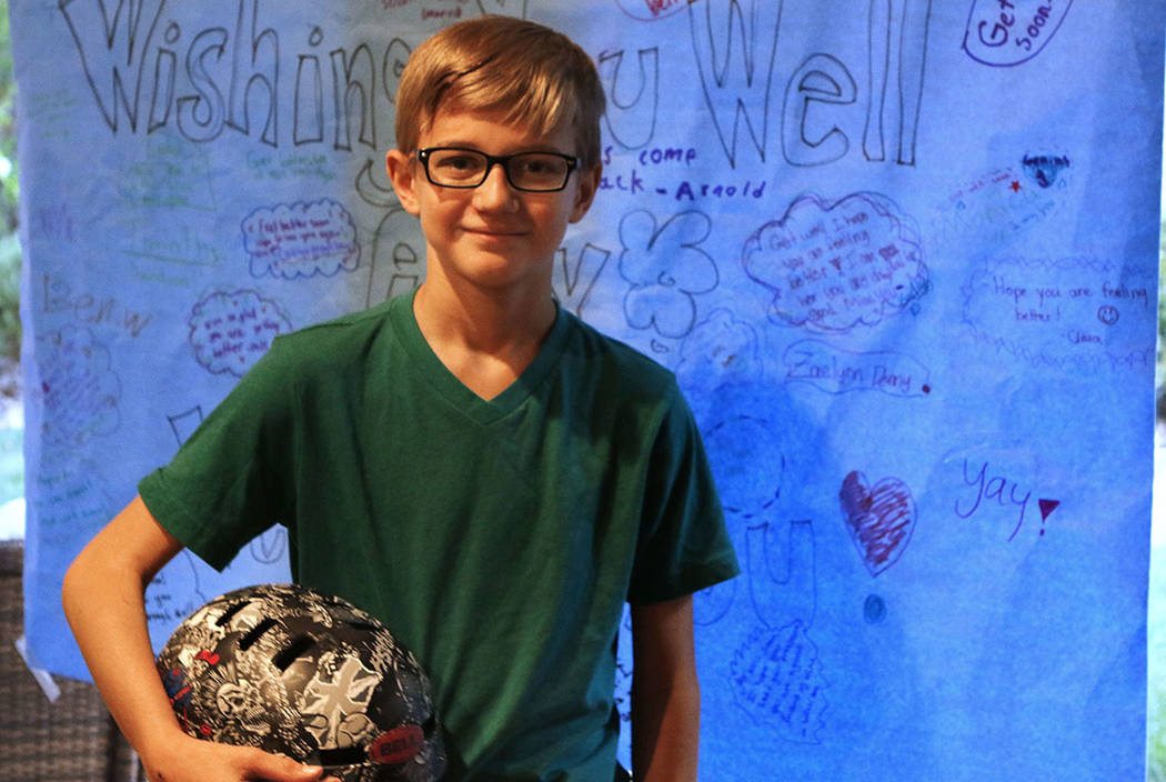 Alex Wigg holds the helmet he was wearing when he was struck by a car on his way to school on April 27. The poster hanging behind him was signed by his classmates. Max Michor Las Vegas Review-Journal