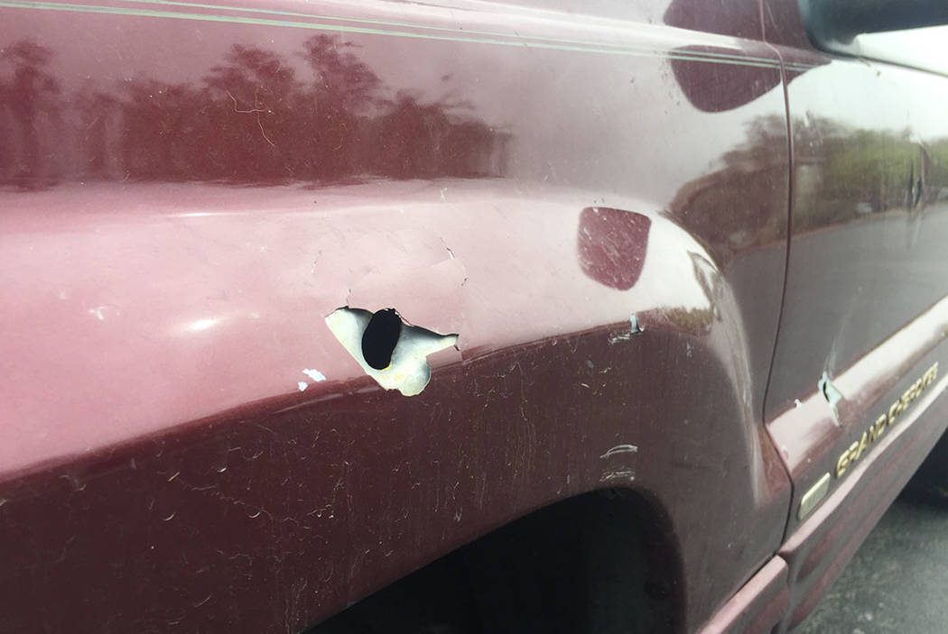 A bullet hole is seen Sunday in the front fender and door of a truck on Shreve Avenue in Las Vegas. (Blake Apgar/Las Vegas Review-Journal)