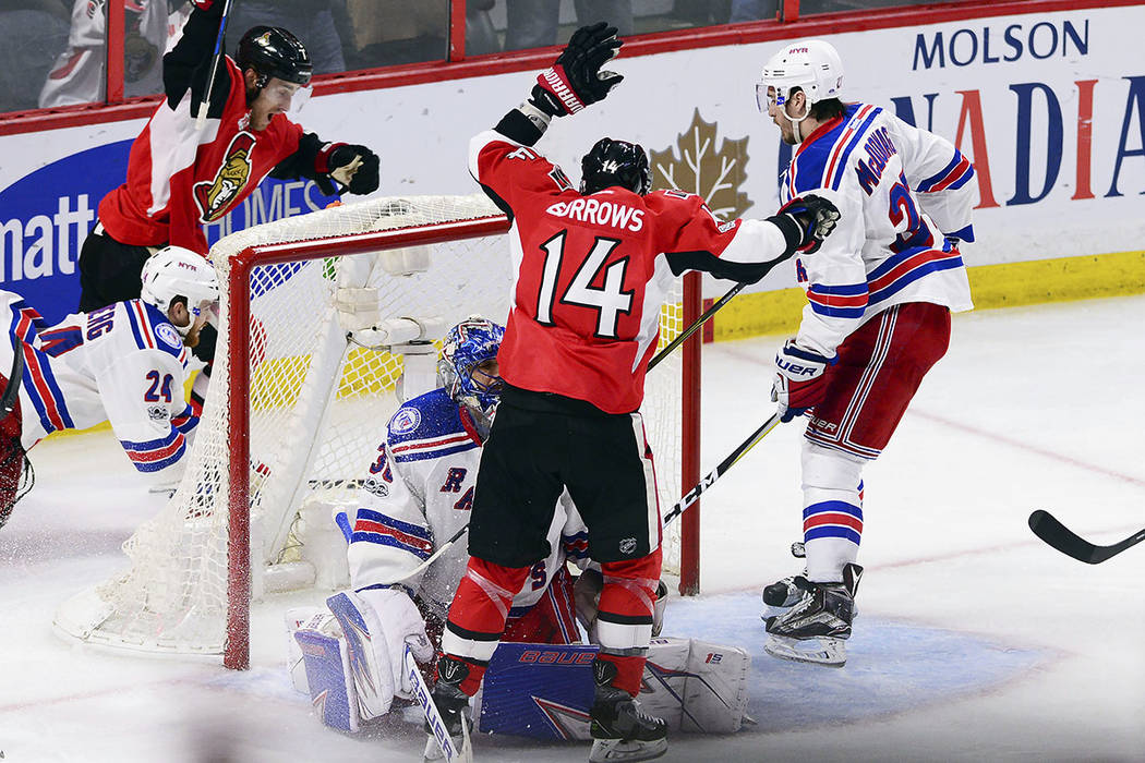 Ottawa Senators center Kyle Turris, top left, and Alex Burrows (14) celebrate after Turris scored the game-winning goal during overtime against the New York Rangers in Game 5 in the second round o ...