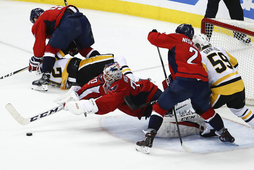 Washington Capitals goalie Braden Holtby (70) dives on the puck with Washington Capitals defenseman Matt Niskanen (2) and Pittsburgh Penguins center Jake Guentzel (59) pushing in during the third  ...