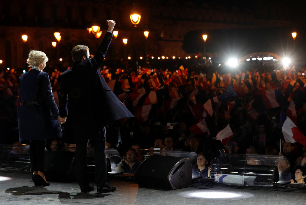 French President-elect Emmanuel Macron and his wife Brigitte Trogneux celebrate on the stage at his victory rally near the Louvre in Paris, France May 7, 2017. REUTERS/Philippe Wojazer